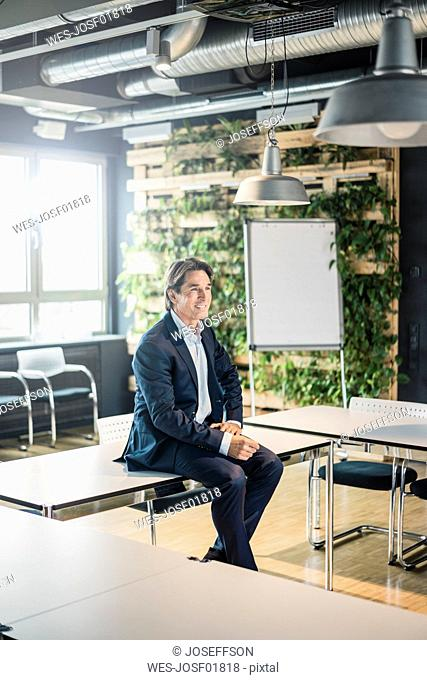 Smiling businessman sitting on table in meeting room of an office