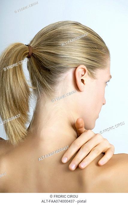 Woman rubbing neck, rear view