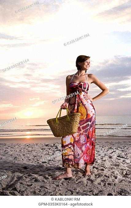 Young woman in colorful sundress standing on beach at sunset