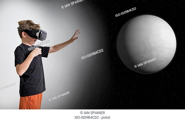 Young boy wearing virtual reality headset, reaching out to touch planet, digital composite