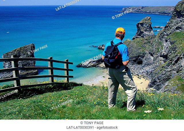 Near Newquay. Man/ hiker. Backpack/ rucksack. Fence. Coastline. Beach. Sea. Summer time