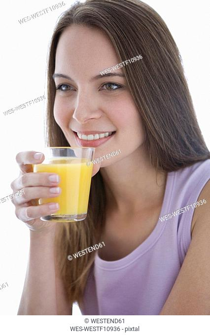 Young woman holding glass of juice, portrait, close-up