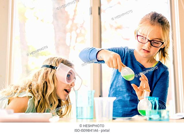 Two girls doing science experiment, shaking liquid in flask