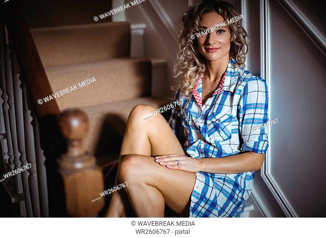 Portrait of beautiful woman sitting on staircase