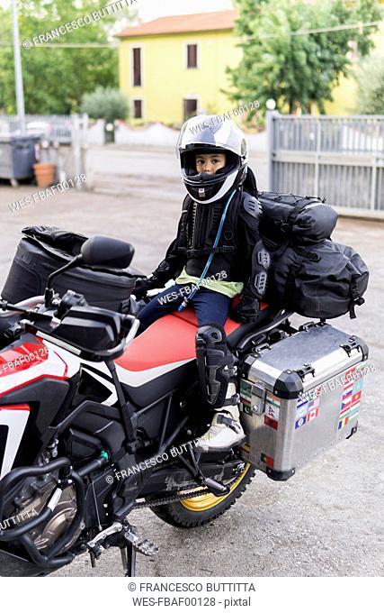 Boy sitting on pillion of a motorbike