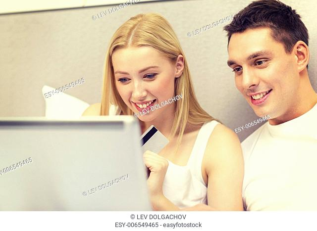 hotel, travel, relationships, technology, internet and happiness concept - smiling couple in bed with laptop and credit card