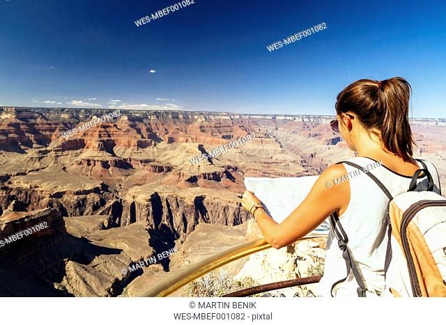 USA, Arizona, young woman with map orientating in front of Grand Canyon