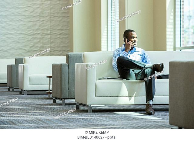 Black businessman talking on cell phone in office lobby