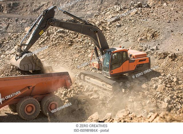 Quarry worker operating heavy machinery in quarry