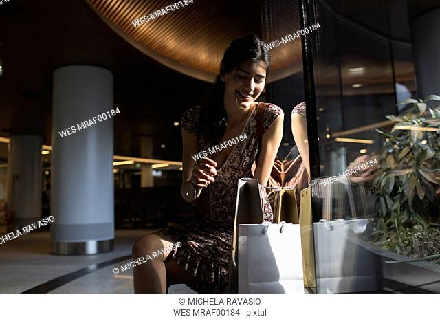 Smiling woman sitting looking into shopping bag
