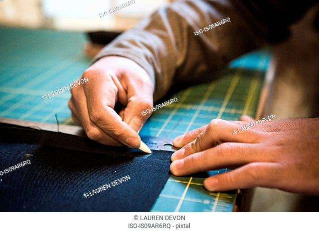 Hands of tailor marking fabric with chalk on workshop bench