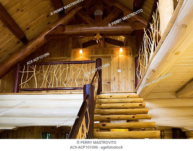 White pinewood stairs with cedar branch railings leading to the mezzanine inside a cottage style log home, Quebec, Canada