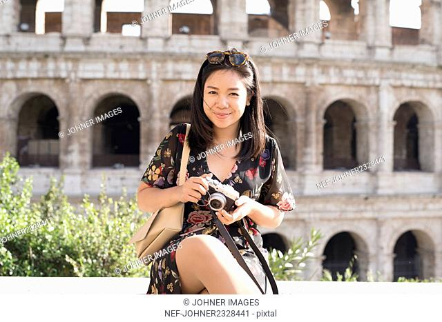 Young woman sitting in front of Coliseum, Rome, Italy