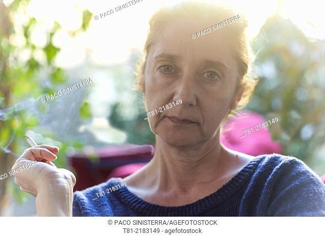Woman smoking quietly in the garden, Javea, Alicante, Valencia, Spain