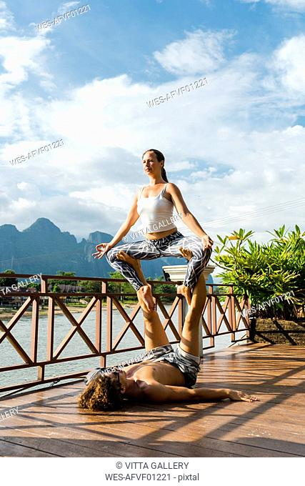 Laos, Vang Vieng, Young couple doing acro-yoga on a terrace