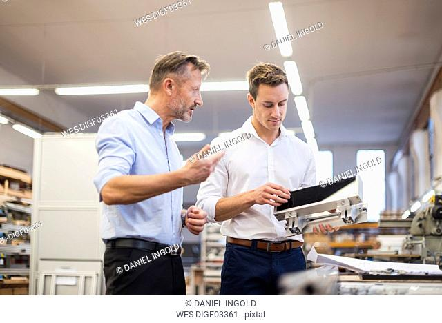 Two businessmen in factory discussing product