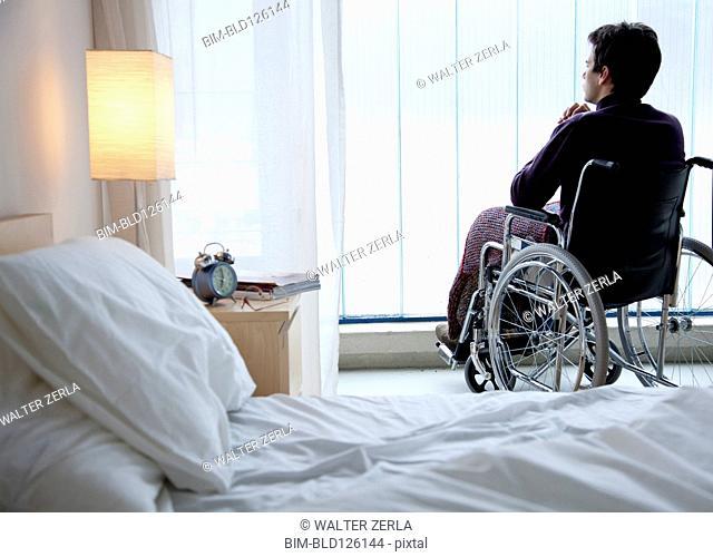 Pensive Caucasian man in wheelchair by window