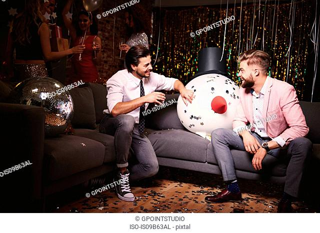 Two men sitting on sofa at party, giant snowman head in-between them, laughing