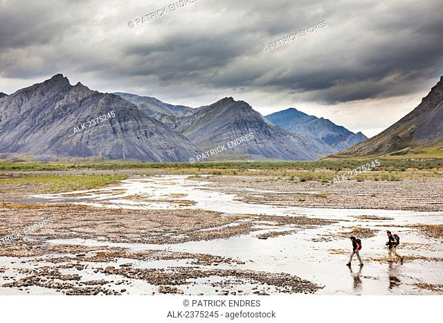 Hikers cross the Marsh Fork of the Canning river which comprises the western border of the Arctic National Wildlife Refuge in the Brooks range mountains, Alaska