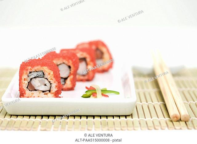Maki sushi rolled in red flying fish roe, close-up