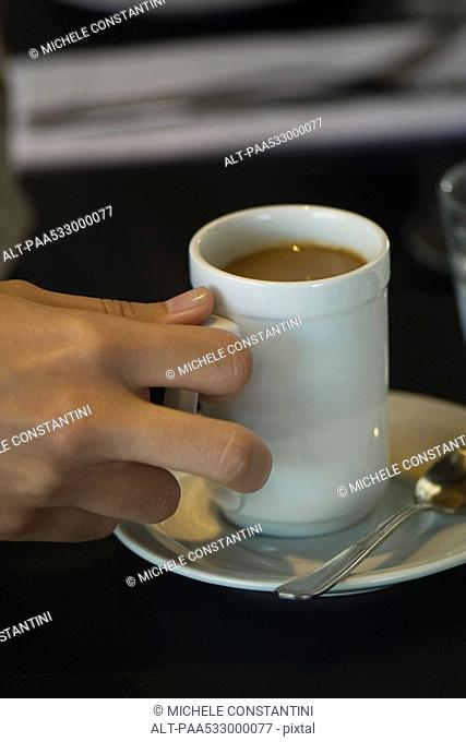 Woman's hand picking up cup of coffee, close-up