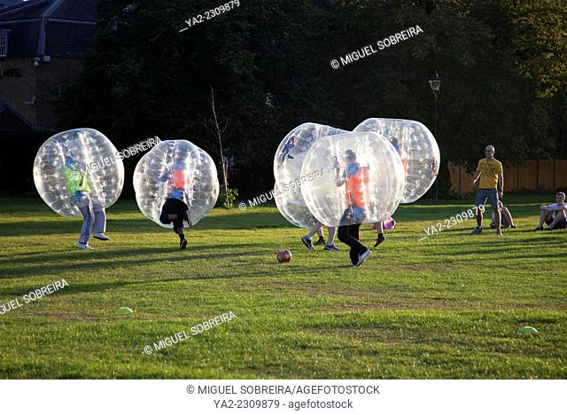 People Zorbing and Playing Football on Clapham Common at Sundown - London UK