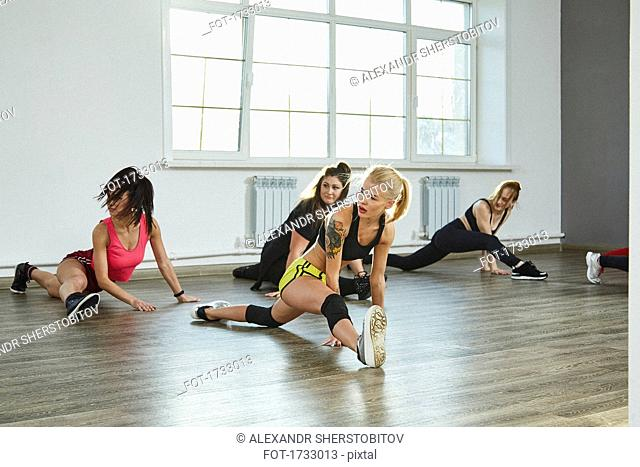 Confident young females practicing splits while dancing in studio