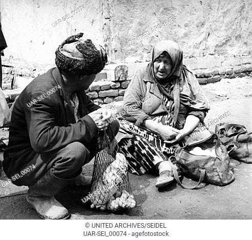 Ein Mann und eine Frau auf dem Basar in Buchara in Usbekistan, Sowjetunion 1970er Jahre. A man and a woman on the bazar at Bukhara in Uzbekistan, Soviet Union