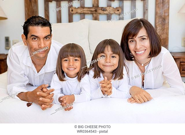 parents and two daughters on bed