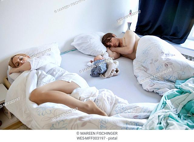 Parents lying with newborn baby in bed