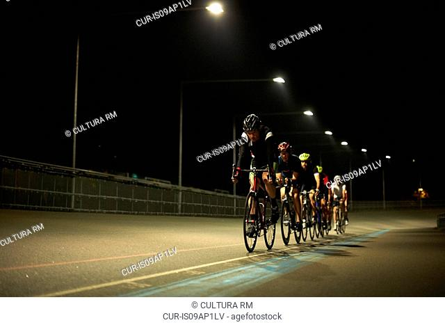 Cyclists cycling on track at velodrome, outdoors