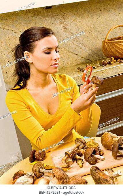 Young woman peeling and cutting mushrooms