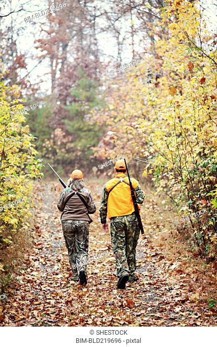 Hunters in camouflage carrying rifles in forest