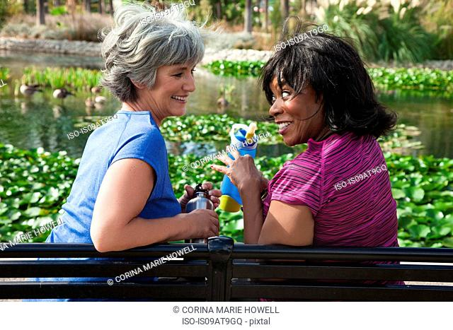 Two mature female friends sitting on park bench, laughing