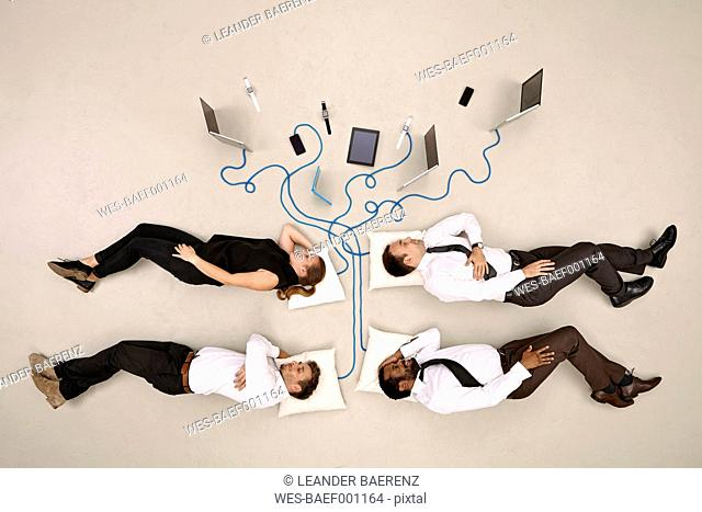 Four business colleagues sleeping connected to mobile devices