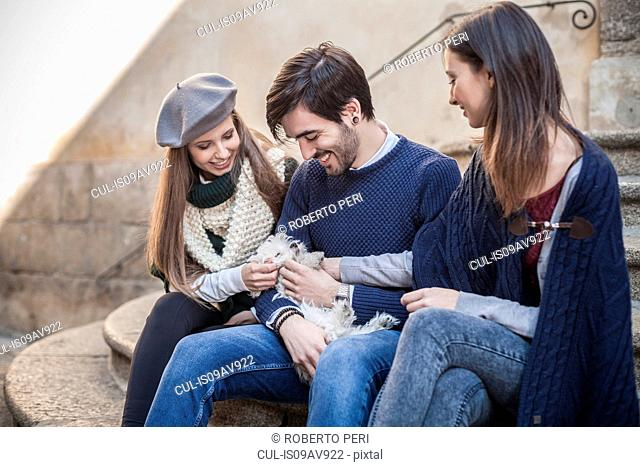 Friends sitting side by side on steps holding fluffy dog looking down smiling