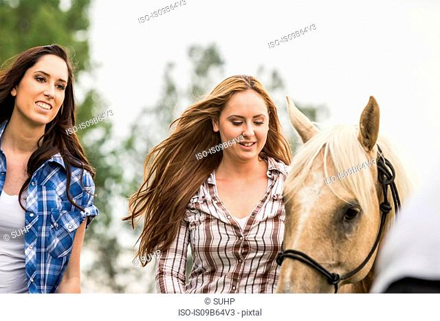 Two young women outdoors, walking with horse, smiling