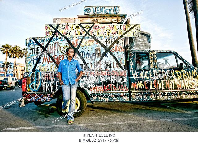 Older Black woman standing by decorated truck