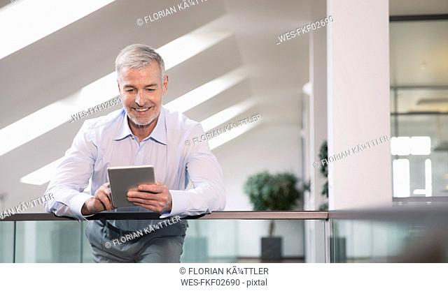 Successful businessman standing at railing in his office, using digital tablet