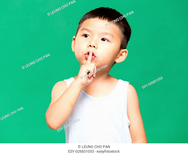 Little boy putting a finger on lips