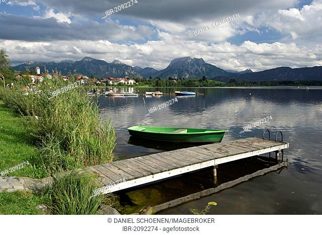 A wooden jetty and a boat on lake Hopfensee near Fuessen, Allgaeu, Bavaria, Germany, Europe