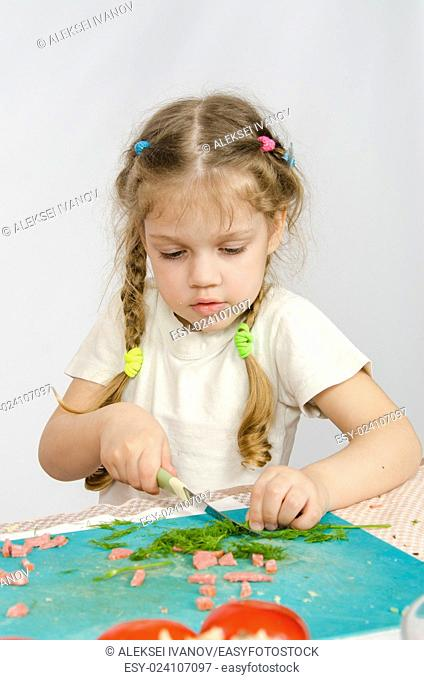 Little six year old girl intently trying to cut with a knife green kitchen table