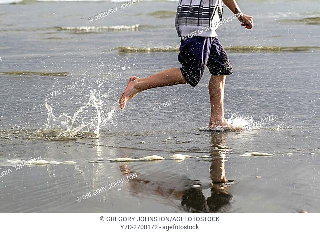 Boy runs along beach and makes splashes in the water at Pacific Beach in Washington