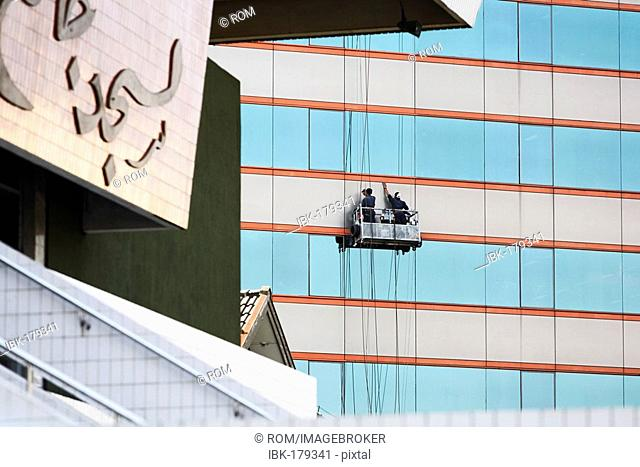 Window cleaner at multistory building in Semerang, Central-Java, Borneo, Indonesia