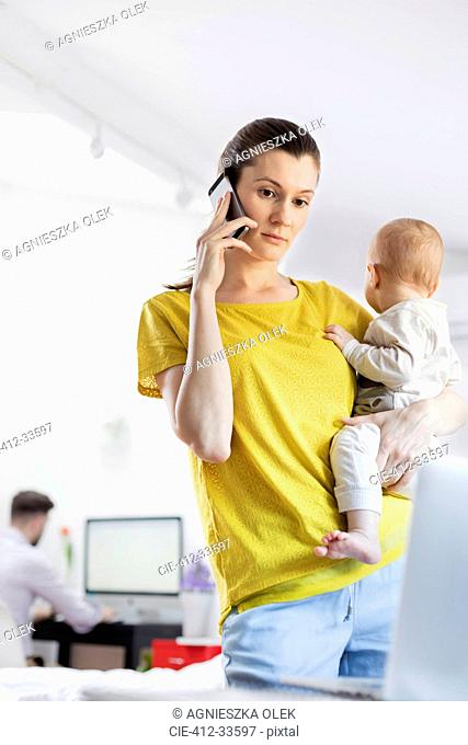 Mother holding baby daughter and talking on cell phone at laptop