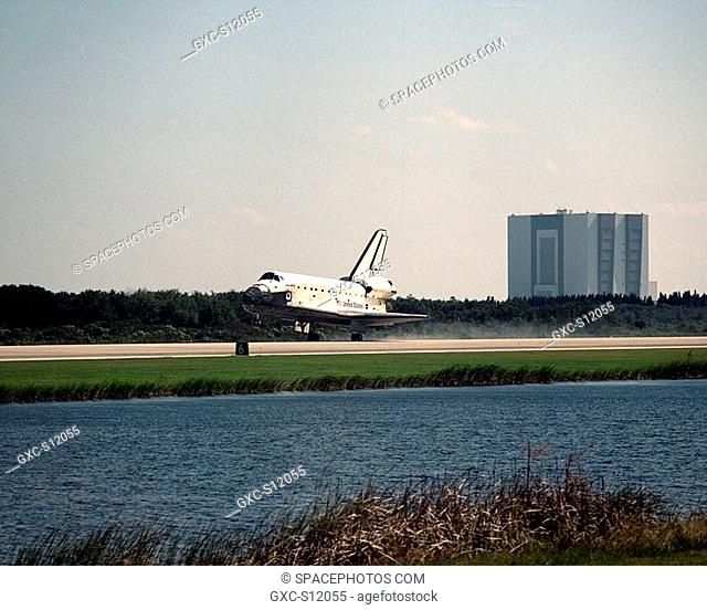 11/07/1998 --- Viewed across the creek bordering runway 33, orbiter Discovery touches down at the Shuttle Landing Facility after a successful mission of nearly...