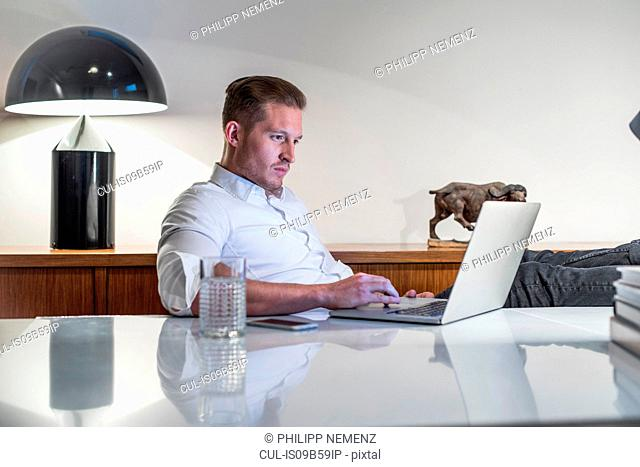Young businessman at desk typing on laptop