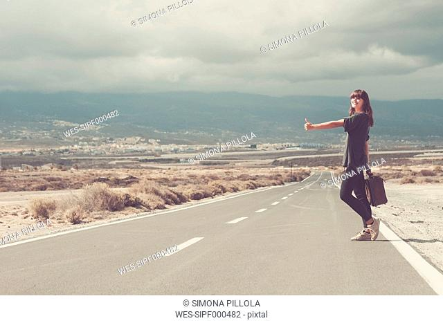 Young woman with suitcase hitchhiking on road
