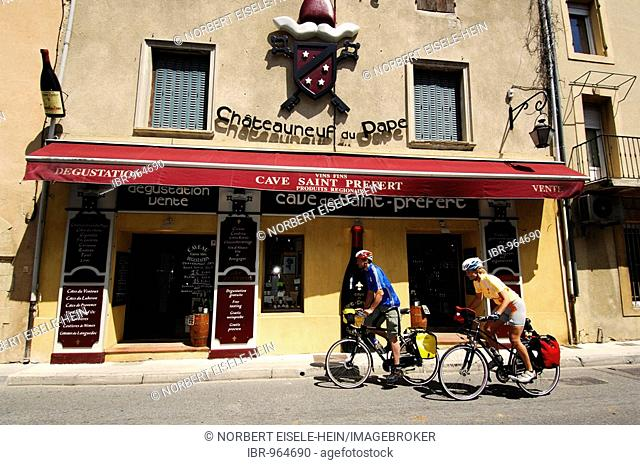 Cyclists passing a wine cellar in Chauteauneuf du Pape, Provence, France, Europe