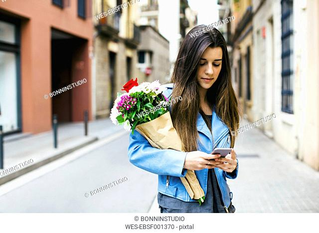 Young woman holding cell phone and bunch of flowers in the city